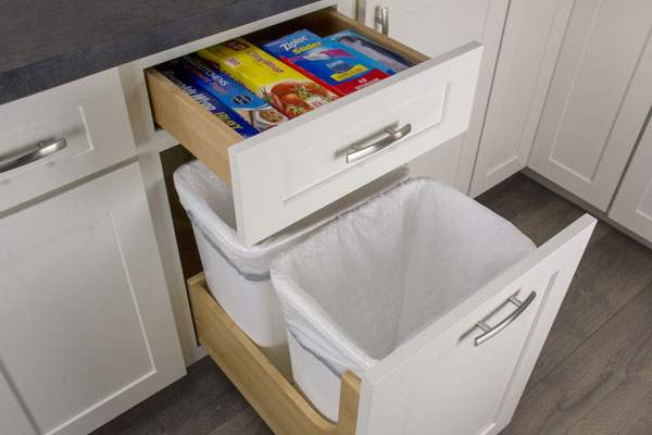 Empty wastebaskets in an open wastebasket cabinet. Above it, a drawer is open containing boxes.