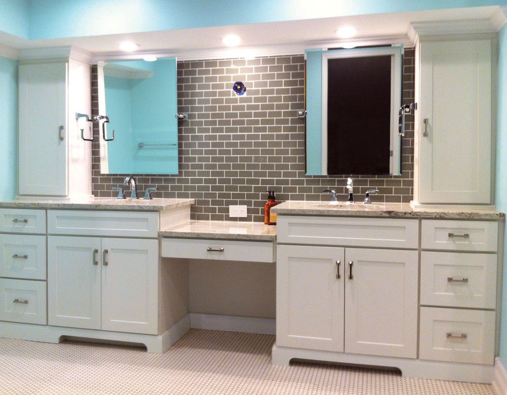 double vanity features low counter between sink units and stacked cabinets on ends, built of white shaker semi-custom cabinets with furniture detailing